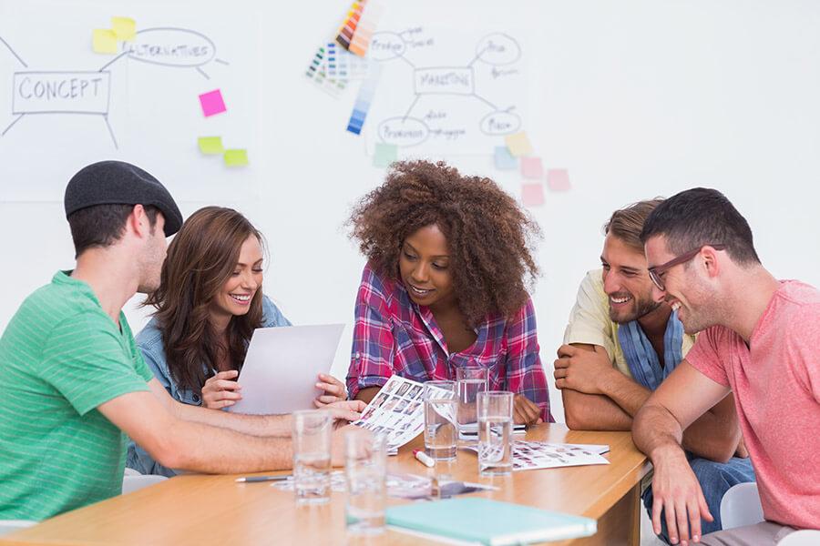 Qué es la dirección de arte. Un director artístico revisa diseños con otros miembros de un equipo creativo.